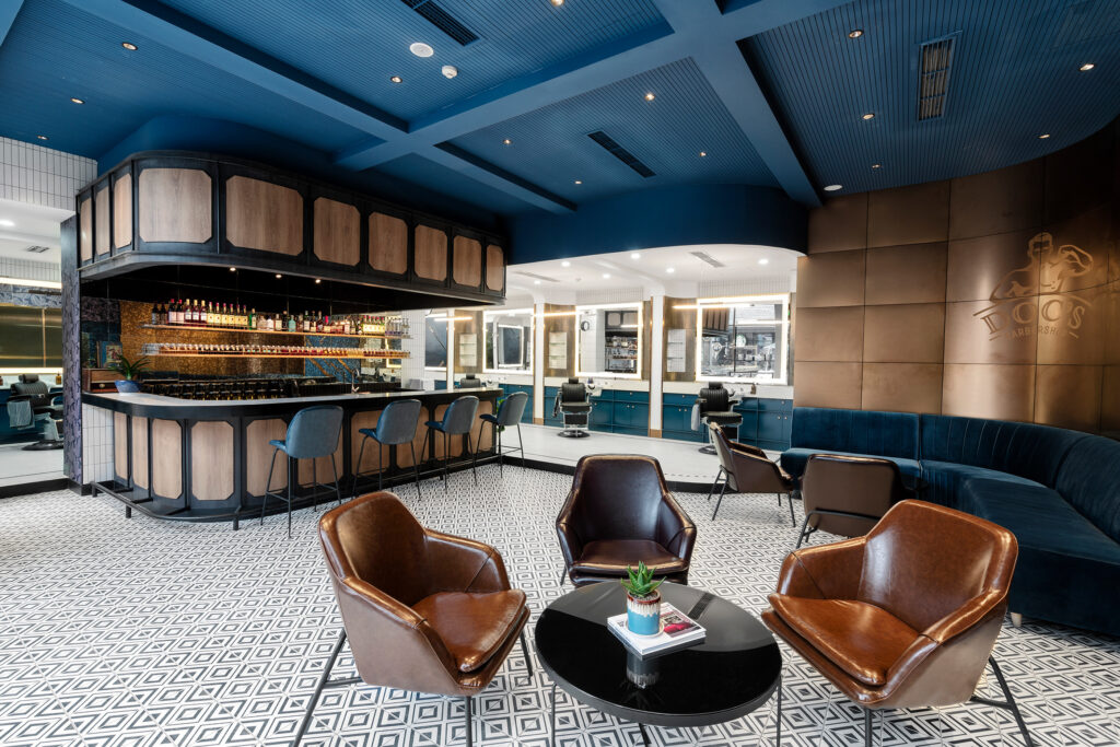 blue, brown & white colored barbershop with small brown chairs & wood-framed bar in center of the room. A blue velvet sofa off to the right