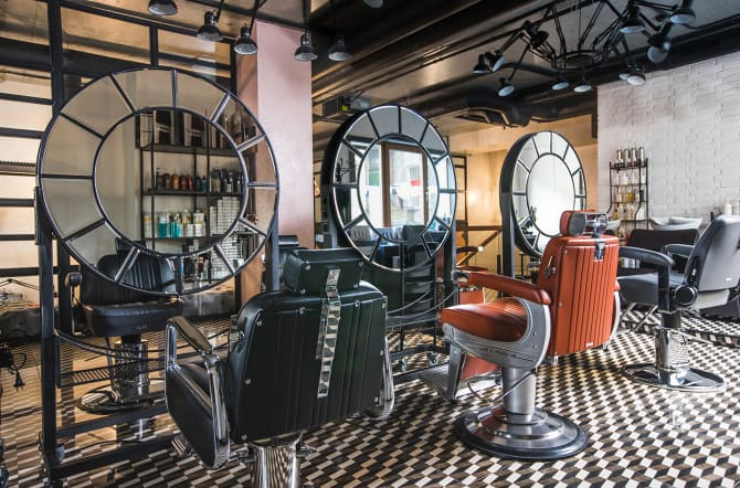 loft style barbershop with coffee area, lounge area, brick walls, stairs, & grey, orange, black chairs. Round tiled mirrors. Black & white tiled carpet.