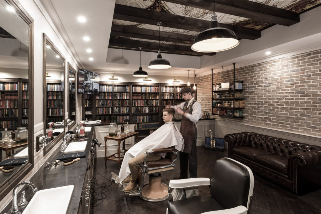 vintage style barbershop with brick walls, book shelves, & world map on the ceiling. Brown & white color scheme.