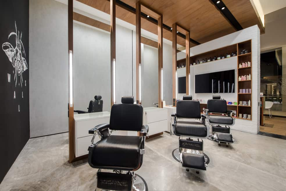 modern barbershop with wood syle walls & floor - black wall with logo painted on it & client chairs in the center of the room separate by floor-to-ceiling sized mirrors